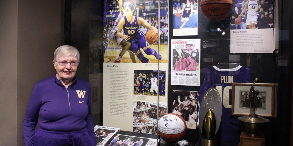 Karen Koon in front of the Kelsey Plum display in the Husky Hall of Fame