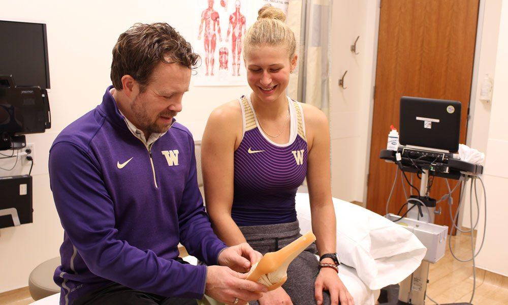 Dr. Hank Pelto shows knee model to Marlee Blue